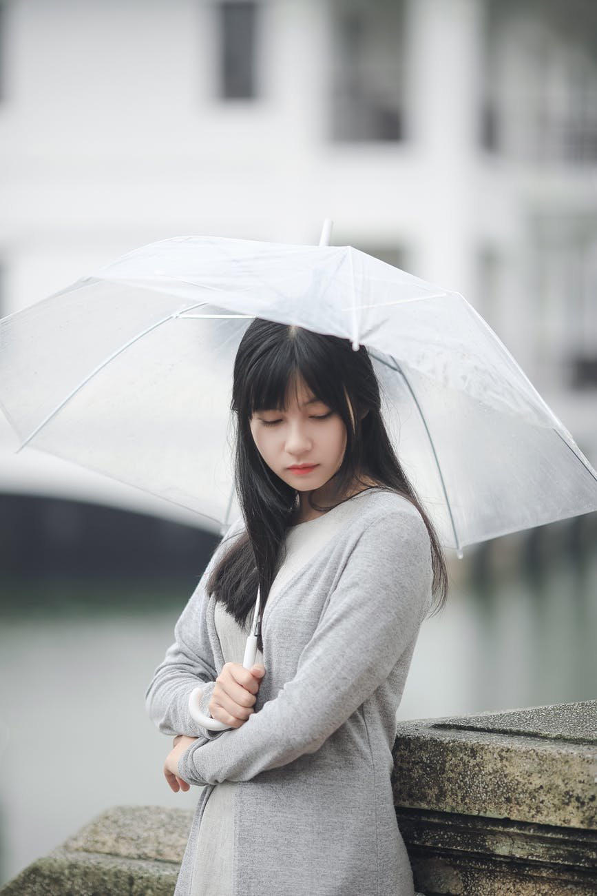 woman wearing gray sweater holding clear umbrella